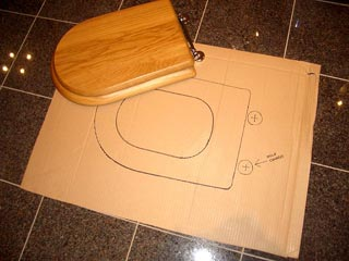 A toilet seat being used to create an outline for the toilet seat template