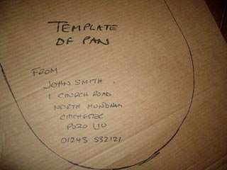 A toilet seat template marked with a name, address and phone number